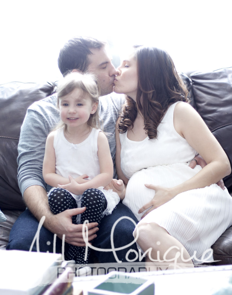 Cute maternity family photo, mom and dad kissing.