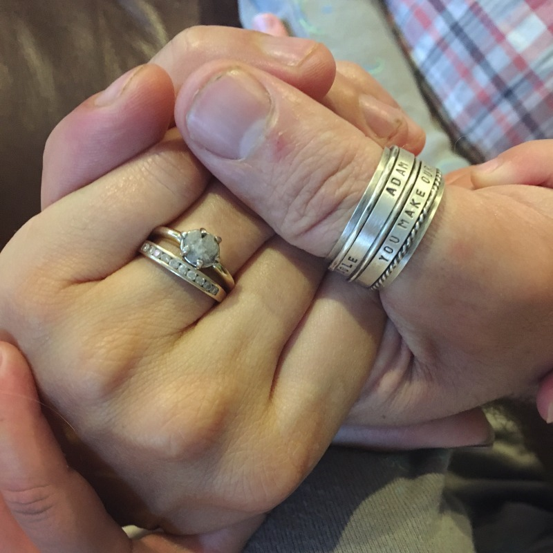 Our anniversary rings, with Colton holding our hands together <3